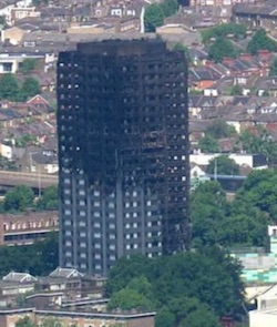 A picture of Grenfell Tower, a 24-storey block of flats, after the fire; half of one visible side and most of the other is charred and windows are missing.