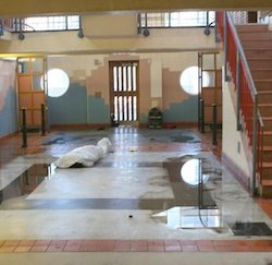 The lobby of a building with a tiled floor with puddles of water on it, with a tiled wall at the back with a cream, light orange and light blue pattern. A stairway with a red guard rail rises on the right.