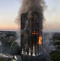A picture of Grenfell Tower, a 24-storey housing block, on fire. The outside is charred and there are flames behind many windows. Water is being sprayed at the tower from multiple directions from below.