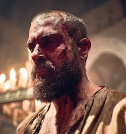 A picture of Tom Cullen, a white man with short hair and a thickish moustache and beard, with a bloodied face, in a mediaeval church