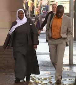 A picture of a Black woman wearing a long grey overcoat and a white headscarf walking along a street next to a Black man of similar age wearing an orange shirt with a beige jacket and trousers.