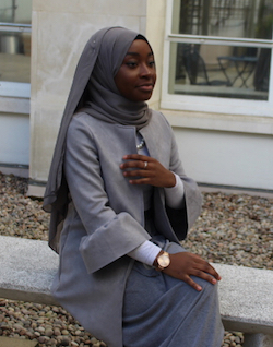 A picture of Hafsah Dabiri, a young west African woman wearing a grey wrap-around headscarf, a smart jacket in lighter grey and a skirt in a slightly darker shade of grey sitting on a concrete bench. A college building is behind her.