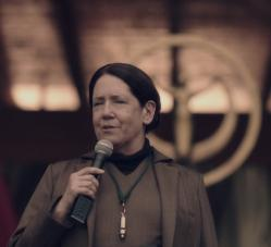 Picture of a late-middle-age white woman wearing a brown hooded robe with a whistle round her neck and holding a microphone in her hand.