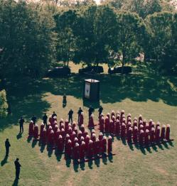 A scene set in a green field with trees surrounding it, with women in identical red robes kneeling on the grass in rows and columns, with armed men in black surrounding them.