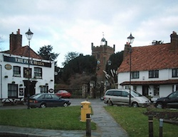 A village green in Harmondsworth behind which is a church; to the left is a pub, the Five Bells, and an old house is to the right. Cars are parked on roads outside the pub and house and a yellow litter bin is in the foreground.