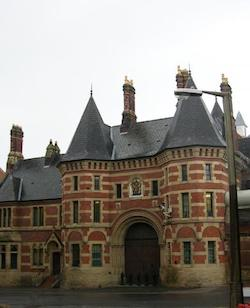 A view across the street to the front entrance of Manchester prison, a Victorian, red-brick, castle-like construction with several steeple-like chimneys and a large archway in the middle, the entrance to which is obstructed by five black bollards.