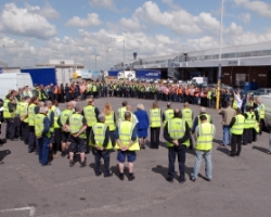 A group of people in yellow flourescent jackets standing in a circle in an open space marked for parking spaces, with cargo sheds behind them with some large vehicles in front of them