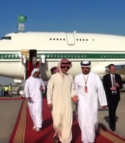 "A picture showing four men, three in traditional Arabic clothing and a fourth wearing a suit and tie, walking down a red carpet away from a large aeroplane in white ""Kingdom"" livery with three green stripes, the thickest of them around the main row of windows."