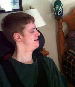 Picture of Hunter Dunn, a young white man with cerebral palsy, wearing a green jumper, sitting in a wheelchair looking to his left (at an off-picture computer screen)