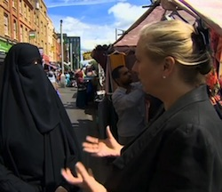Still of a woman wearing a black headscarf and niqaab, with only her eyes showing, on the left and a white woman with her hair clipped at the back, wearing a black jacket, on the right