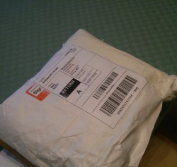 Picture of a white package sealed with packing tape with a label addressed to Amazon
