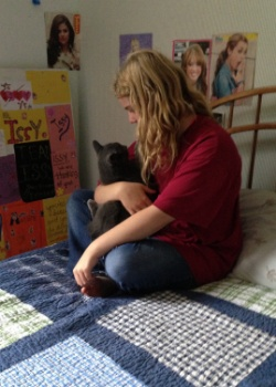 Picture of a young girl in a red sweater holding a black cat