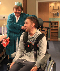 Picture of Jackson Walsh from Emmerdale in hospital, sitting in a manual wheelchair, with mother standing behind him