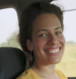 A still of Jennifer Brea, a light-skinned mixed-race woman with short brown hair, wearing a yellow blouse, sitting in a car seat.
