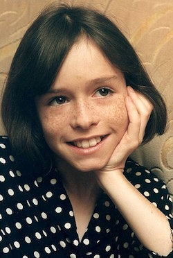 Picture of a 10-year-old white girl (with a distinctly boyish face) with freckles, long dark hair and a black blouse with white dots.