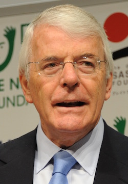 Picture of John Major, an elderly white man with white hair, wearing glasses with thin rims, a white shirt, blue tie and dark-coloured jacket