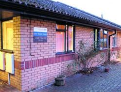 Picture of John Sharich House, a brick one-storey building with flowerpots outside, with an NHS name plate to the left