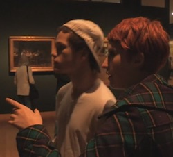 A still in dim light of Josh and Francesca in an art gallery, Francesca explaining a Van Gogh painting to Josh