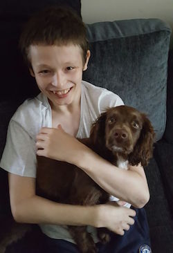 Josh Offer-Simon, a young white boy with short hair, cuddling a small brown dog.