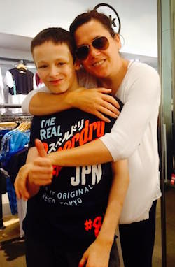A picture of Joshua, a young white boy with short hair and a black Superdry T-shirt with English and Japanese writing on it, being embraced by his mother, a white woman with brown hair, dark glasses on, a white jumper or cardigan and black track-suit bottoms.