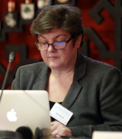 Picture of Julie Bindel, a middle-aged white woman with short, greying brown hair, wearing thick-rimmed glasses and a grey suit jacket with a name badge pinned to it and a low-cut top underneath, sitting typing on an Apple laptop.