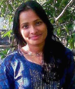 Picture of Jyoti Singh-Pandey, a young South Asian woman with long black hair, wearing a blue dress with columns of white dots down the front, and a necklace.