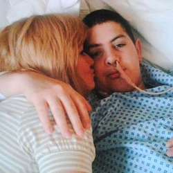 Picture of Kane Gorny, a young man with a tube in his nose wearing a hospital gown, hugging his mother. He died because of negligence at St George's hospital, London