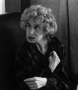 Picture of an old woman with curled hair, wearing an unidentifable dark garment with her arms crossed against her chest
