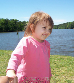 Picture of Katie McCarron in a pink top with flowers, standing on grass in front of a lake. Someone off-camera is holding her hand.