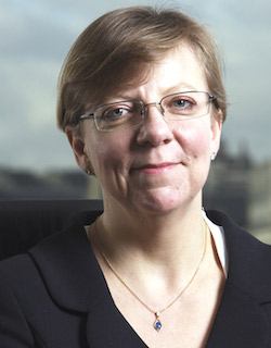 Picture of Katrina Erskine, a middle-aged white woman wearing thin-rimmed glasses and a dark suit jacket