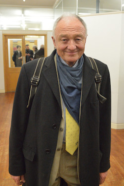 Picture of Ken Livingstone wearing a dark grey jacket, a yellow tie with a logo partly visible, and a blue scarf round his neck under his jacket. He is walking through a corridor with wooden doors with glass windows behind him.