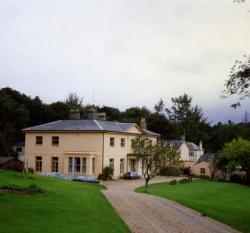Picture of Kesgrave Hall, a Georgian mansion in England. The building is surrounded by a field on the right and a set of grassy slopes and an outbuilding on the left. There is a driveway in the foreground and cars parked in the car park behind the building, in the left of the picture