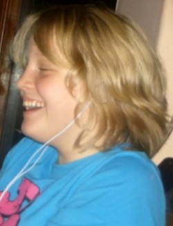 Picture of Chloe, a white teenage girl with blond hair, wearing a turcquoise sweatshirt with pink writing on it, wearing headphones and smiling