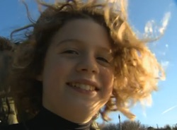 Picture of Oli, a young white boy with wavy blond hair which glistens in the sun