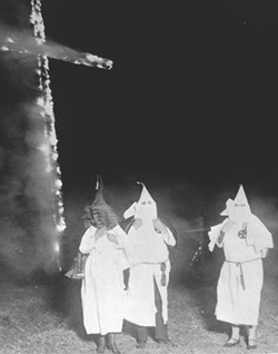 A black-and-white image of three members of the Ku Klux Klan, two women and one man, in white sheets and masks, standing by a burning cross.