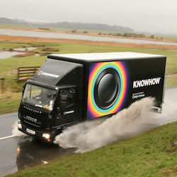 "A black Iveco Eurocargo truck with the Knowhow logo of a black button with rings in rainbow colours in circles around it, with the words ""Knowhow, the service available at Curry's PC World""."