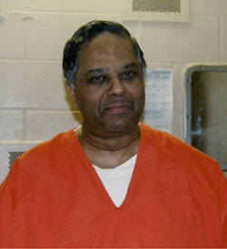 Picture of Krishna Maharaj, an elderly dark-skinned South Asian man wearing orange prison clothes
