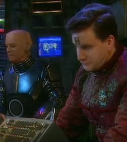 A picture of Kryten (an android) and Arnold Rimmer sitting in front of some controls on a spaceship, in the BBC comedy Red Dwarf.