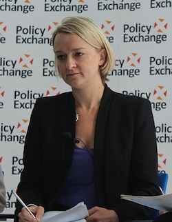 Picture of Laura Kuenssberg, a white woman in her 30s with shortish blonde hair, wearing a blue top with a black suit jacket over it, with a backdrop composed of the logo of Policy Exchange