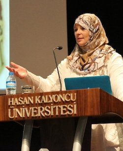 "A picture of Lauren Booth, a middle-aged white woman wearing a cream headscarf with blue and brown patterns on it, standing against a lectern with the Turkish words ""Hasan Kalyoncu Üniversitesi"" on it."