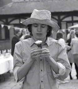 Black and white picture of a young white man with a straw hat on and rolled-up shirt sleeves, holidng an ice-cream cone in his hand, standing in front of a timber-framed building.