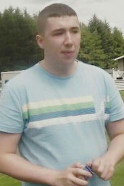 Lee Irving, a young white man with very short hair wearing a light blue T-shirt with white, green, dark blue and white stripes, in what appears to be a garden with a house and fir trees behind him.