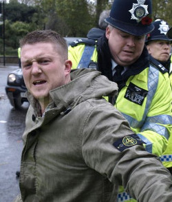 Picture of Stephen Lennon (who calls himself Tommy Robinson), leader of the EDL, with an angry and aggressive expression on his face as he is arrested