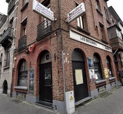 "A red-brick building on a street corner, with the signs reading ""Jupiter: Les Beguines""."