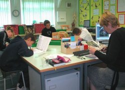 Picture of a lesson (with four pupils clustered around the teacher) at Scarborough Pupil Referral Unit