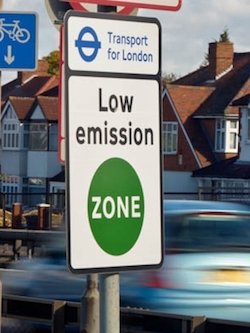"A sign on a London street saying ""Transport for London: Low Emission Zone"". A metallic turquoise car speeds past behind it; some Mock Tudor houses are the other side of the road."