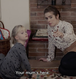 "A still from the film A Silent Child, showing Joanne, a white woman with brown hair wearing a cream-coloured blouse with various symbols dotted over it, a short brown skirt and thick, dark tights, looking at Libby, a four-year-old white girl with blond hair wearing a dark grey dress with little black diamonds dotted over it, pointing towards the camera and telling her ""Your mum's here"" (which is subtitled at the bottom of the screen)."
