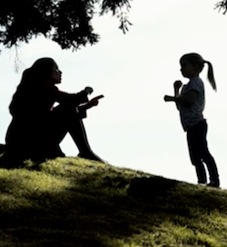 A still from The Silent Child showing Libby and Joanne, a woman and girl, silhoutted under a tree, signing to each other.
