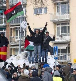 Picture of demonstrators in Libya raising the old national flag