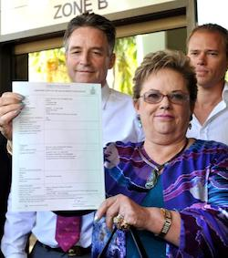 Picture of a light-skinned mixed-race woman wearing a blue and purple patterned blouse, holding an official document in both hands, outside a court building, with two men standing behind her